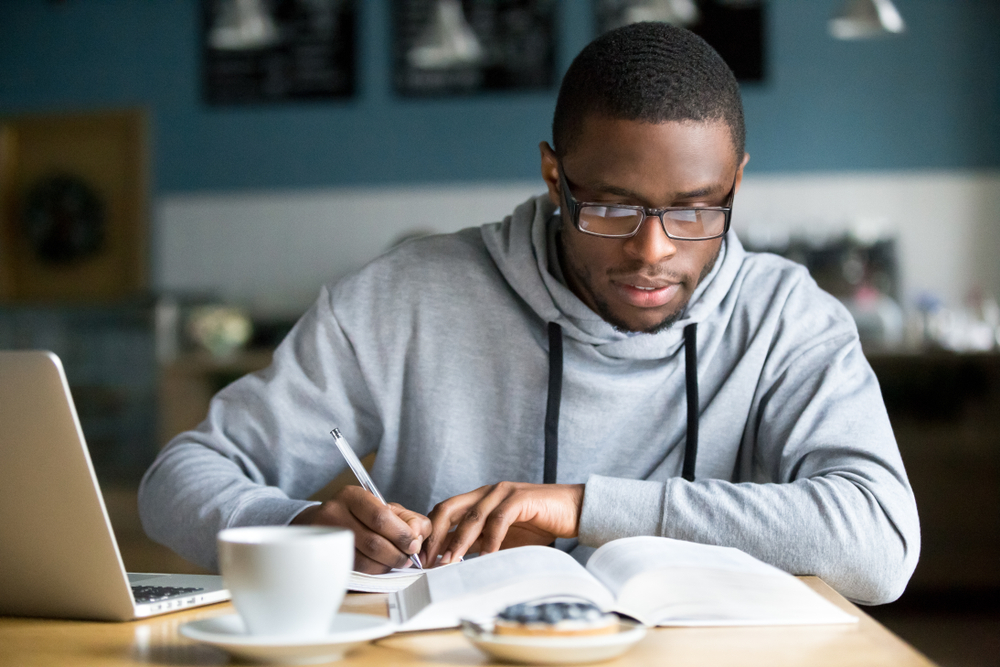 Student wearing glasses focusing on a text book while studying